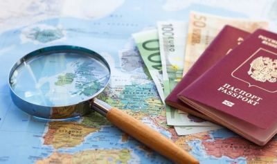 World map with some euros and two passport showing citizenship by investment.