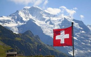 Swizz flag with Alps on the background.